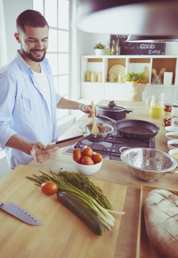 Man following recipe on digital tablet and cooking tasty and healthy food in kitchen at home stock photos