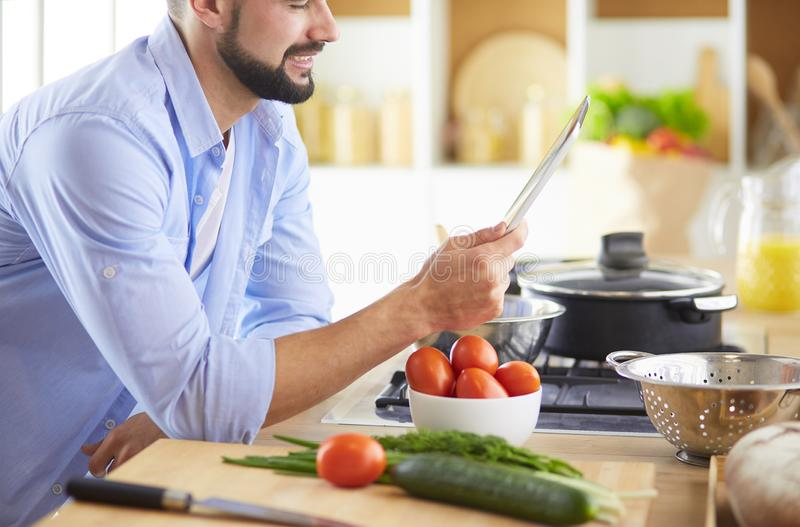 Man following recipe on digital tablet and cooking tasty and healthy food in kitchen at home stock images