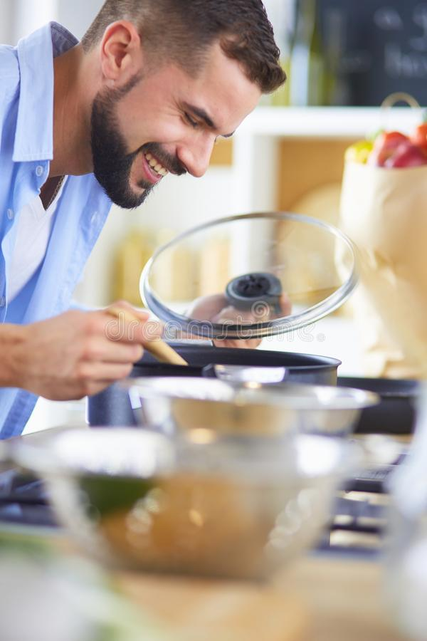 Man following recipe on digital tablet and cooking tasty and healthy food in kitchen at home royalty free stock image