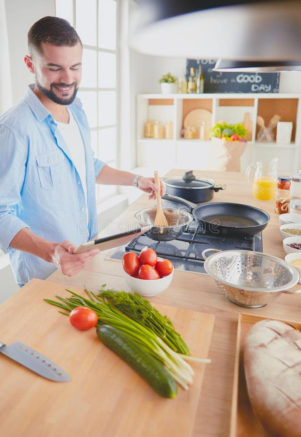 Man following recipe on digital tablet and cooking tasty and healthy food in kitchen at home royalty free stock photo