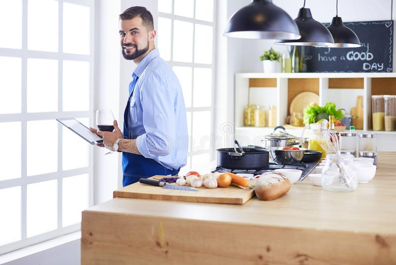 Man following recipe on digital tablet and cooking tasty and healthy food in kitchen at home stock photography