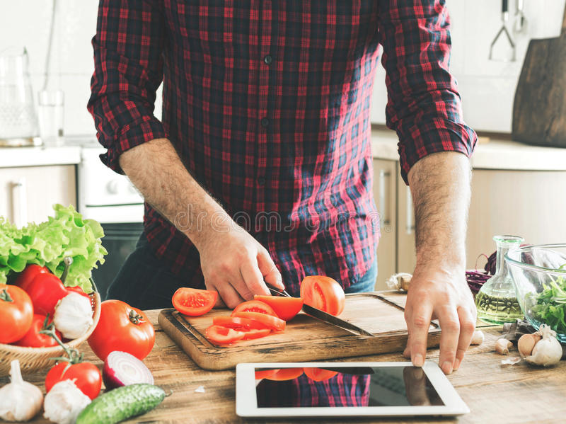 Man following recipe on tablet and cooking healthy food royalty free stock photography