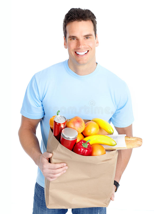 Man with food. Smiling young man holding a shopping bag with food stock image
