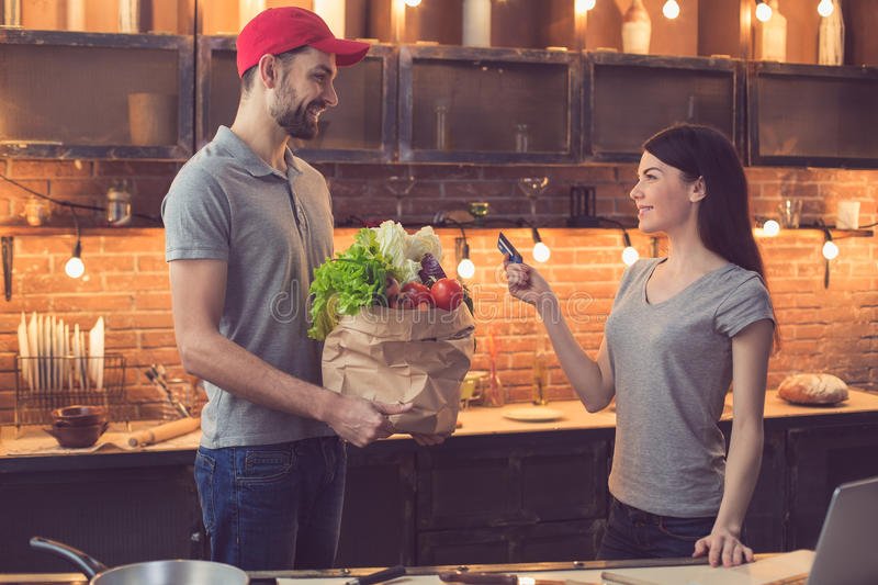 Man with food from food delivery service. Food delivery service. Young men bringing fresh food. Young women paying with credit card. Nice loft kitchen interior stock photo