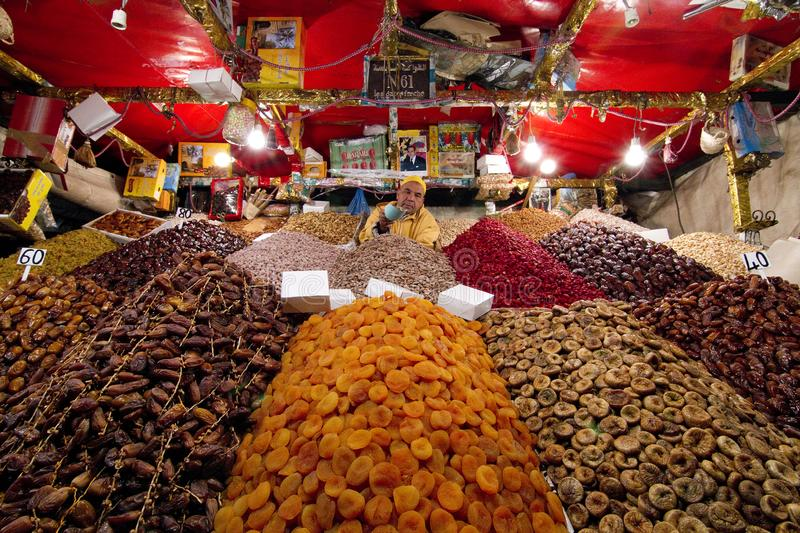 Man in a food stall holding out scoop full of nuts at camera surrounded by vibrant colored fruits and nuts stock photos