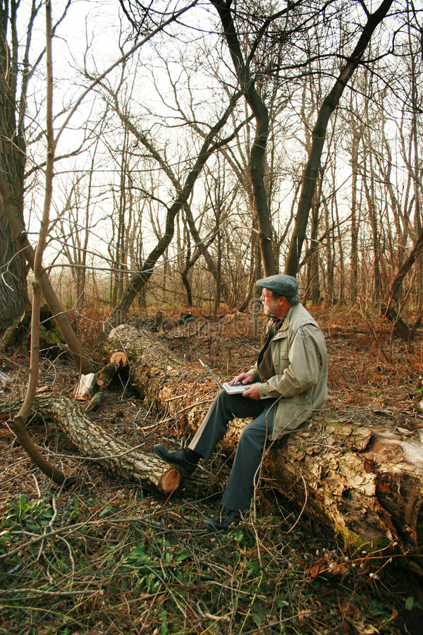 Man in forest with laptop. Adult man in a forest with laptop. Sitting on a log royalty free stock photography