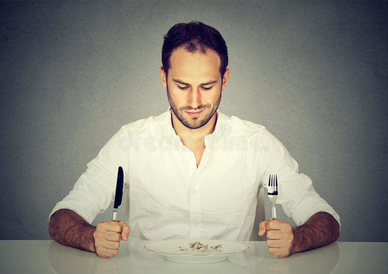 Man with fork and knife sitting at table looking at empty plate royalty free stock photo