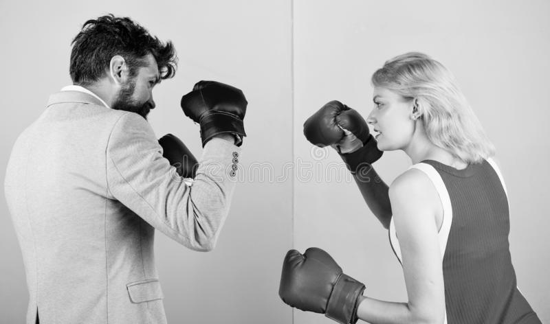 Man formal suit and athletic woman boxing fight. Couple in love competing in boxing. Female and male boxers fighting in stock photography