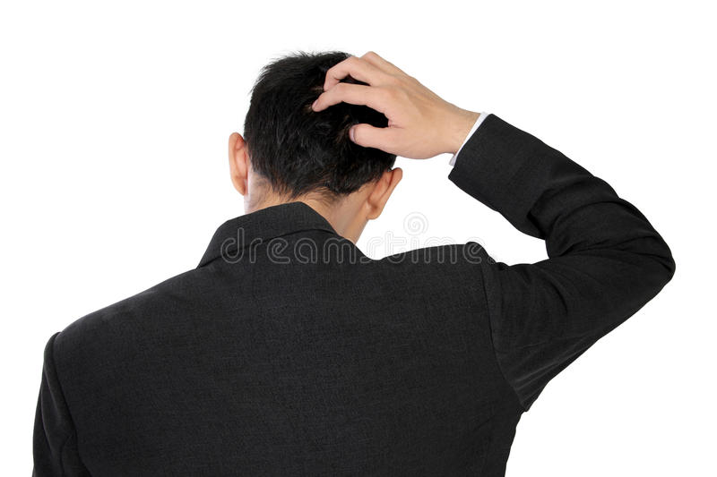A man in formal wear scratching his head in confusion, isolated on white. A man in formal wear scratching the back of his head, expressing stress or confusion royalty free stock photo