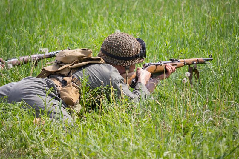 Man in foror of an American soldier during the Second World War with a rifle leading a battle lying in the grass stock photo