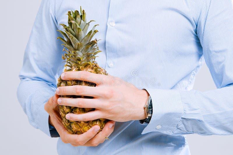 Man& fort x27 ; les mains de s dans une chemise tiennent un ananas images stock