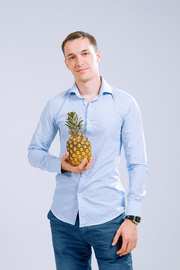 Man& fort x27 ; les mains de s dans une chemise tiennent un ananas image libre de droits