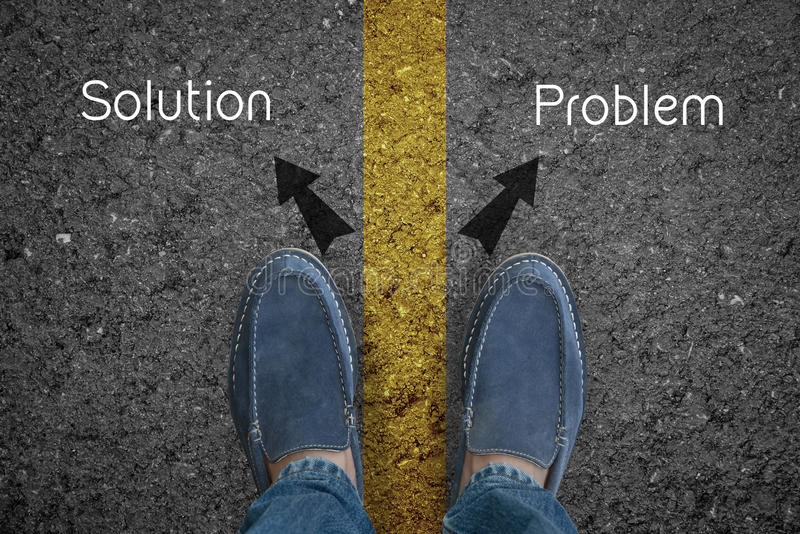 Man fot på asfaltvägen med primat lösnings- och problembegrepp för pil arkivfoton