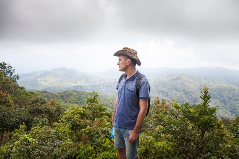 Man fotvandraren på en överkant av ett berg, drinkvatten thailand som löper begrepp av en sund livsstil arkivfoton