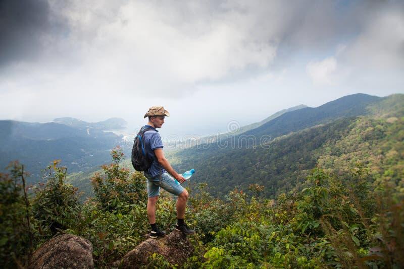 Man fotvandraren på en överkant av ett berg thailand som löper begrepp av en sund livsstil arkivfoto