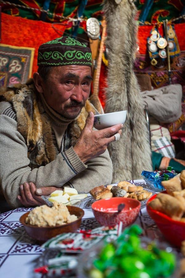 Man från Kazakhsfamiljen av jägare med att jaga den deras insidan för guld- örnar mongolianen Yurts royaltyfri foto