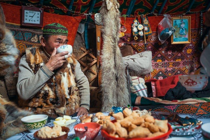 Man från Kazakhsfamiljen av jägare med att jaga den deras insidan för guld- örnar mongolianen Yurts fotografering för bildbyråer