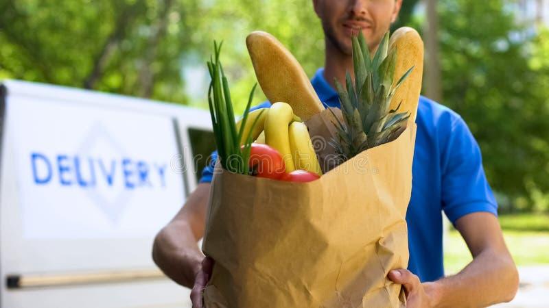 Man från matleveransen som rymmer den fulla påsen av nytt gods, online-lagerservice royaltyfri fotografi