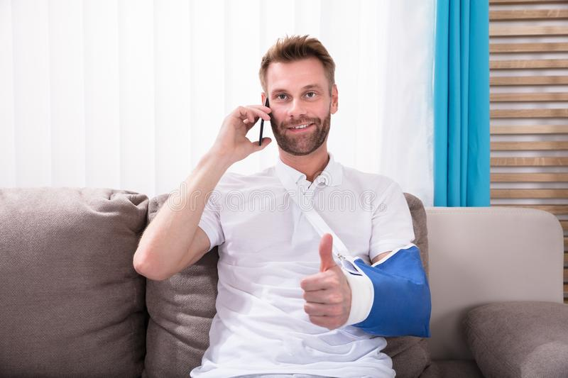 Man With Fractured Hand Gesturing Thumbs Up. While Talking On Mobile Phone stock image