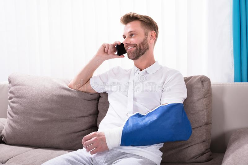 Man With Fractured Hand Talking On Mobile Phone. Young Man With Fractured Hand Sitting On Sofa Talking On Mobile Phone royalty free stock photo