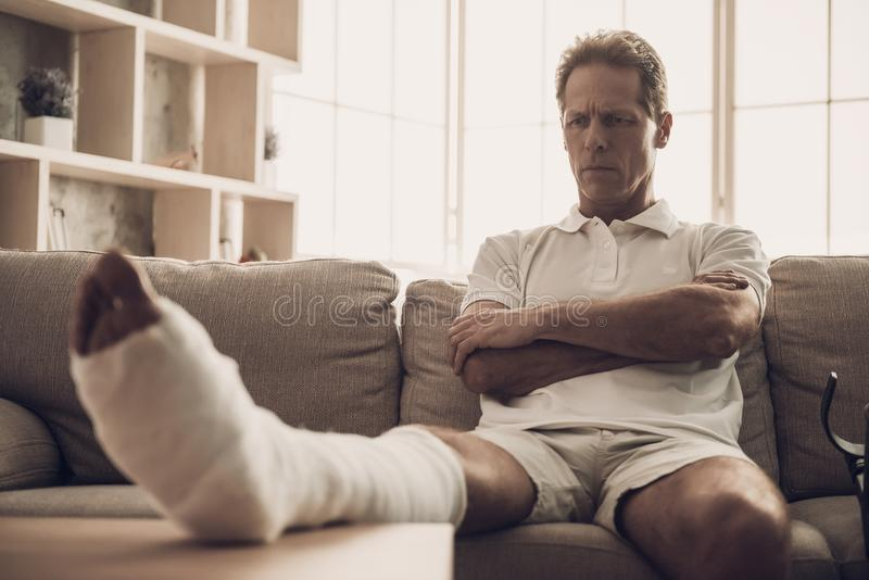 Man With Fractured Leg Sit On Sofa Crossing Arms. Handsome Caucasian Person Feel Pain in Leg in Plaster Cast Posing with Upset Expression. Rehabilitation and stock photography