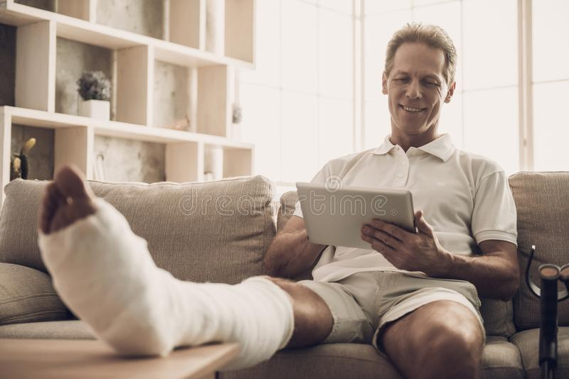 Man With Fractured Leg Sit On Sofa and Use Tablet. Handsome Caucasian Man Broken Leg in Plaster Cast Wearing White Clothes and Posing with Cheerful Expression stock photos