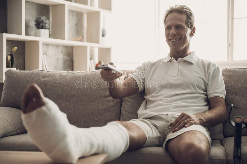 Man With Fractured Leg Sit On Sofa and Watch TV. Handsome Caucasian Person with Foot in Plaster Cast Wearing White Clothes Posing with Cheerful Expression royalty free stock images