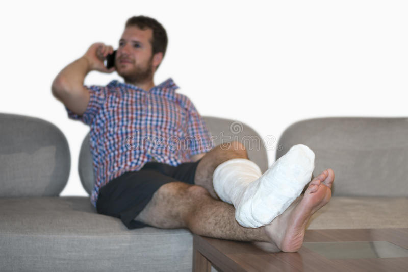 Man With Fractured Leg Sitting On Sofa Talking On Cellphone. Disabled man with broken leg talking by phone stock image