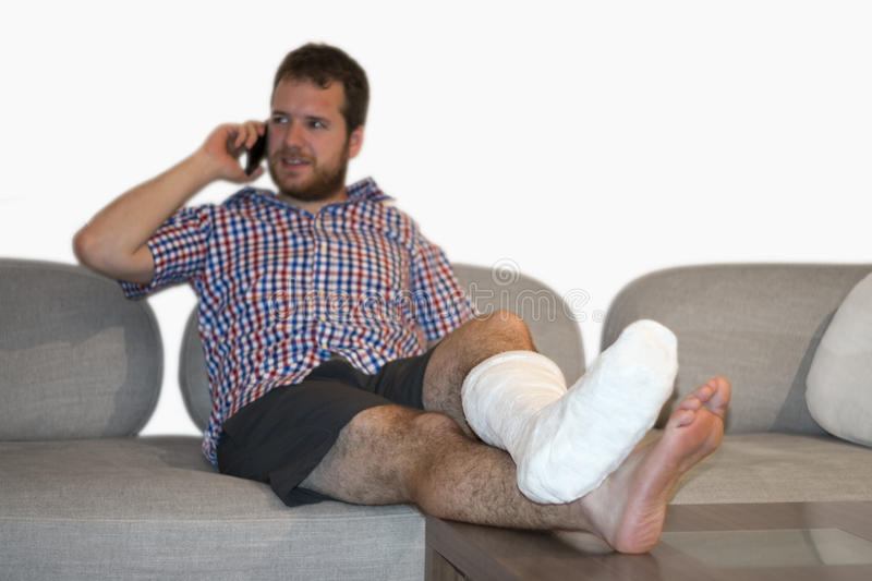 Man With Fractured Leg Sitting On Sofa Talking On Cellphone. Disabled man with broken leg talking by phone stock photos
