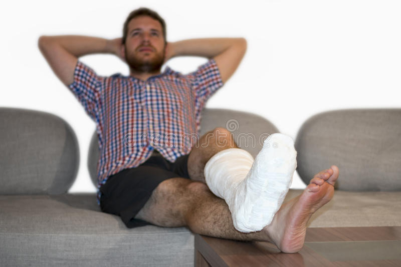 Happy Man With Fractured Leg Sitting On Sofa. Disabled man with broken leg stock photos
