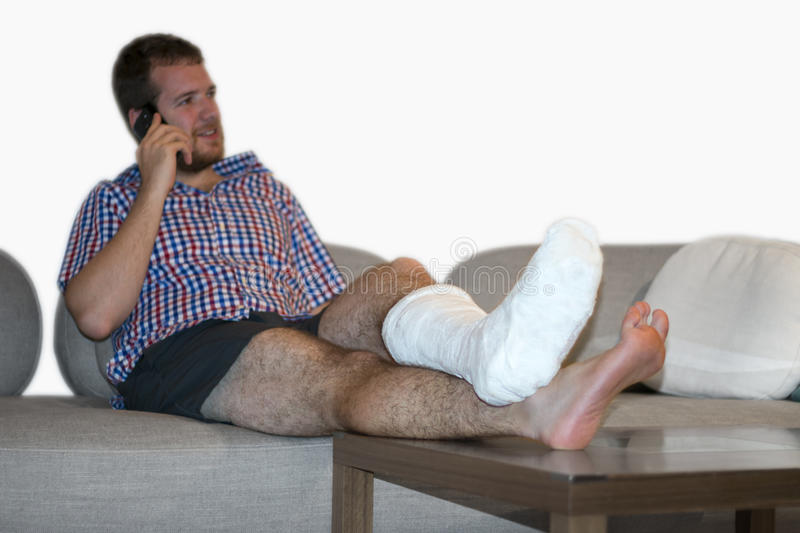 Man With Fractured Leg Sitting On Sofa Talking On Cellphone. Disabled man with broken leg talking by phone royalty free stock images