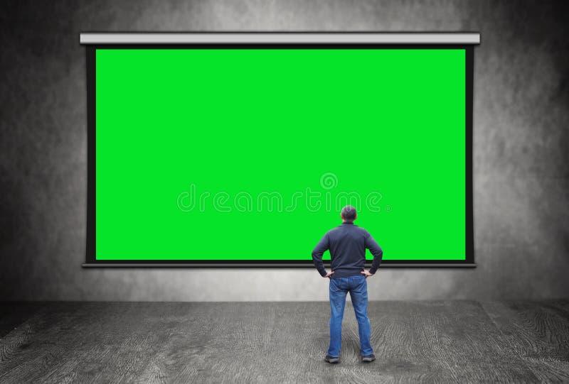 Man framme av den stora tomma gröna skärmen royaltyfria bilder