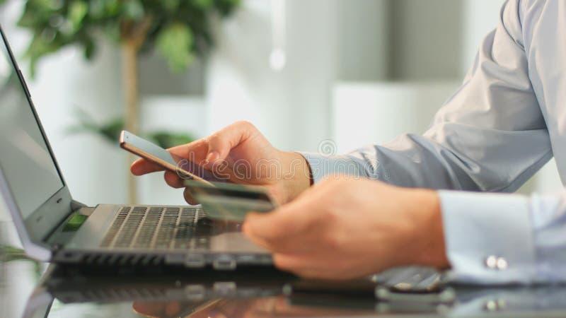 Man framställning av online-betalning från bankkonto, genom att använda mobilen app på smartphonen arkivfoton