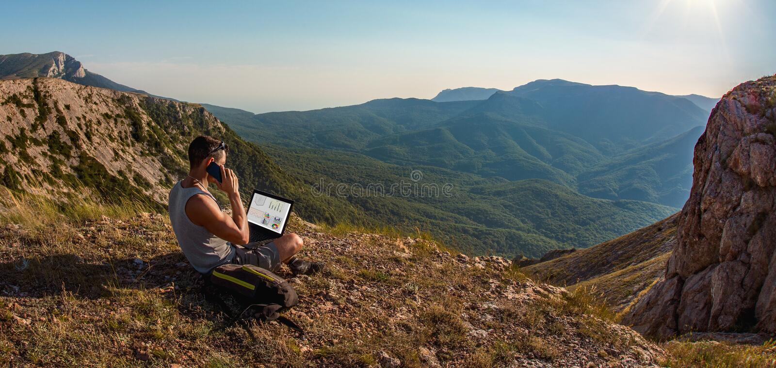 Man freelancer with laptop, call by cellphone, on beauty mountains landscape royalty free stock photography