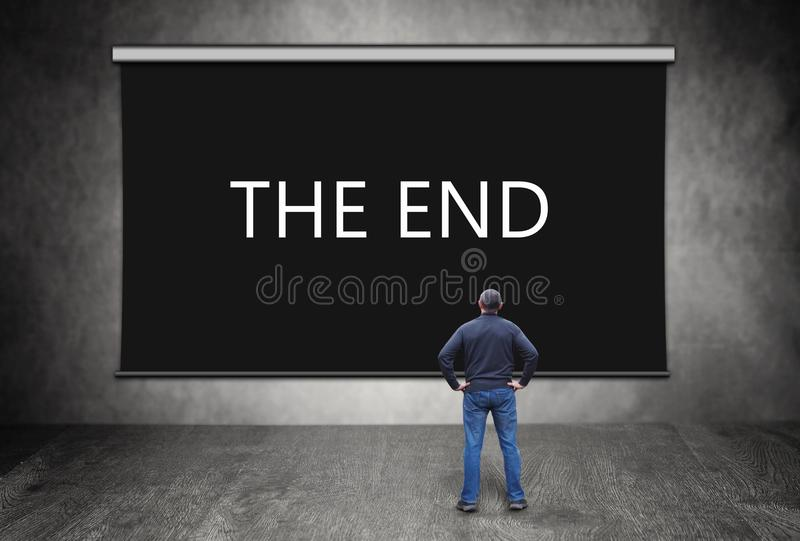 Man in front of black screen with words The End. Man stands in front of black screen with words The End royalty free stock photography