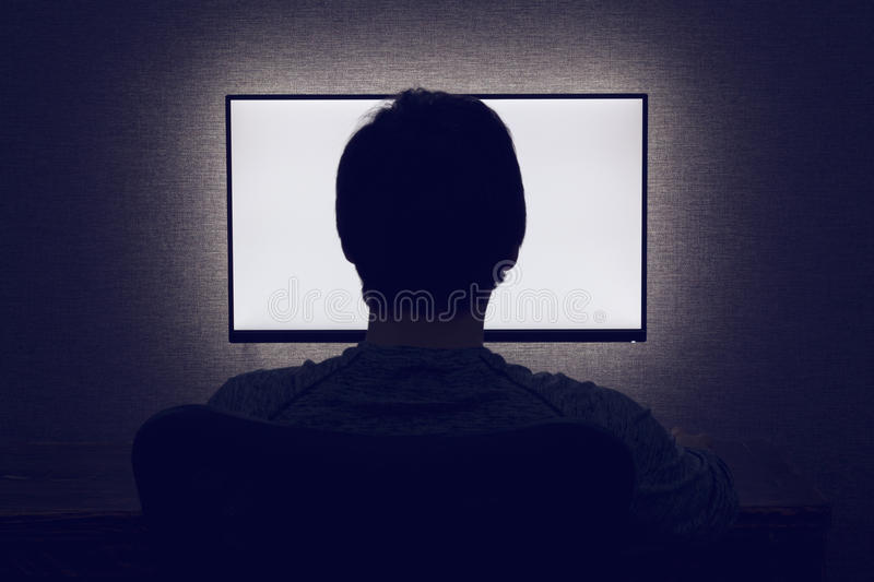 Man in front of a blank monitor. Man sits in front of a blank monitor in dark room royalty free stock photo