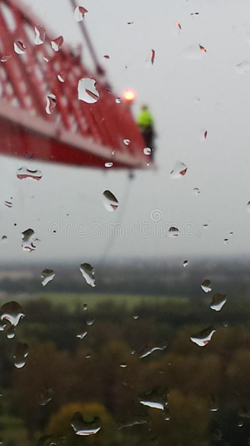 Man on a front jib of a tower crane in a rainy day in London royalty free stock image
