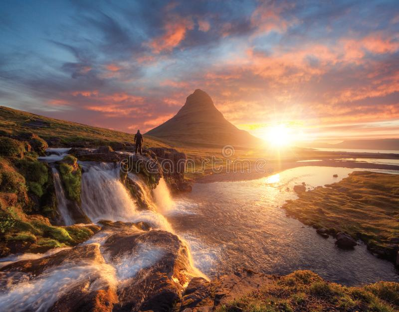 Man in front of Kirkjufell mountain, Iceland stock photo