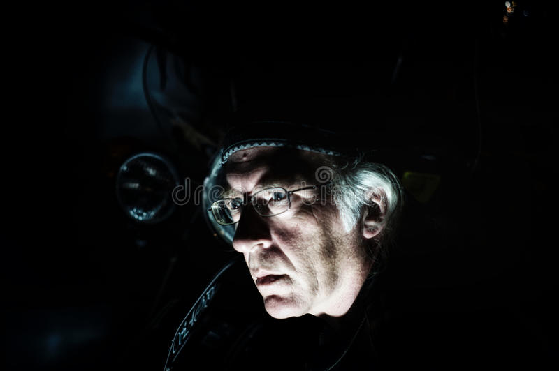 Man in front of motorcycle lit from below royalty free stock photography