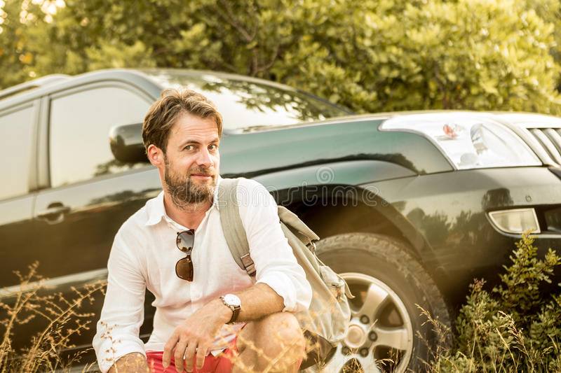 Man in front of SUV car during safari adventure trip. Forty years old caucasian man in front of his four-wheel drive SUV car. Driver having a break outdoor royalty free stock photos