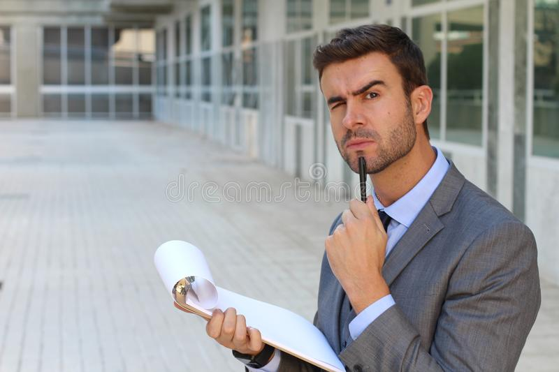 Man frowning while taking notes royalty free stock photo