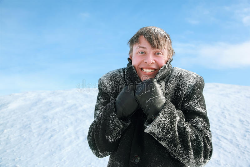 Man froze and hides head in collar of overcoat. Young man froze and hides head in collar of winter overcoat stock image