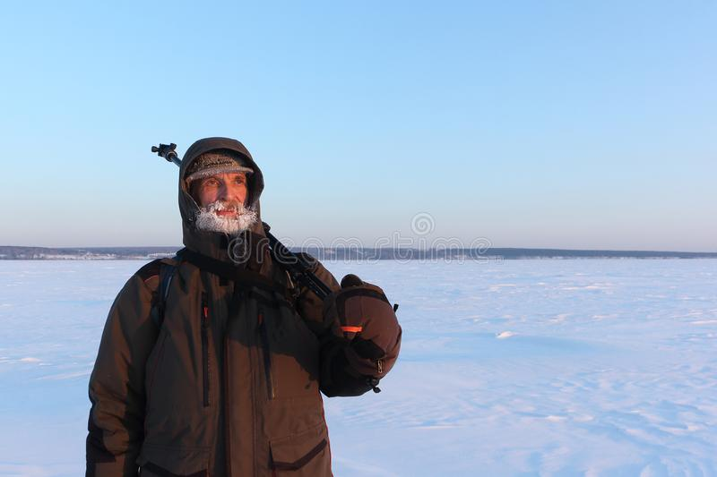Man with a frozen beard and a tripod on his shoulder on a snowy background in the winter at sunset stock photo