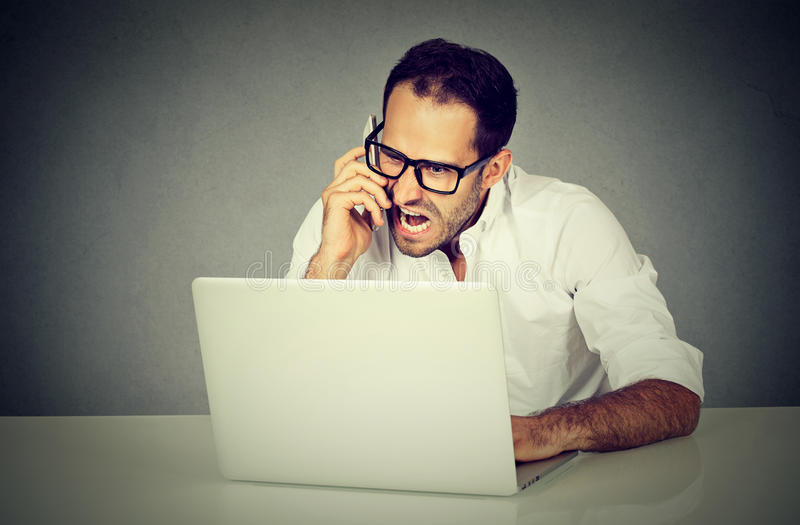 Man frustrated and angry shopping online screaming on phone. Young man frustrated and angry shopping online screaming on a phone. Negative human emotions face royalty free stock photo