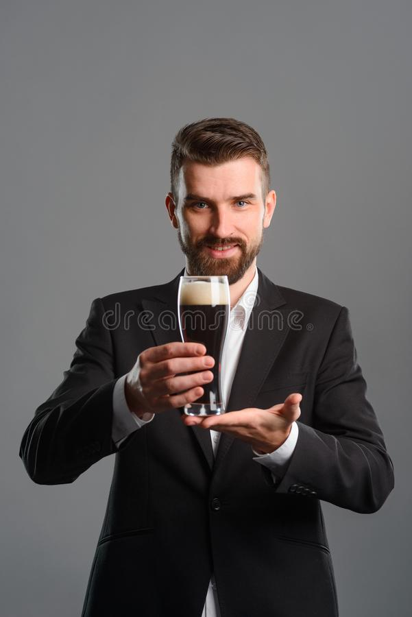 Man with full beer glass. Toothy smile of bearded man in black jacket over white shirt. Holding a glass of dark beer and keeping its bottom with second hand royalty free stock image