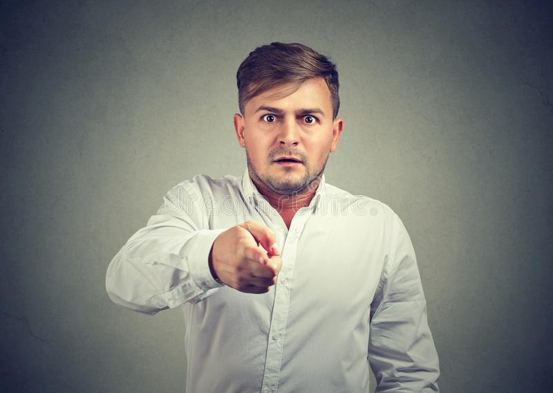 Frightened young man pointing at camera. Man full of fear looking amazed and pointing at camera on gray background royalty free stock photography