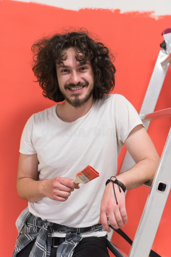 Man with funny hair over color background with brush. Portrait of a beautiful young man with funny hair and brush over color background with copyspace expressing royalty free stock image