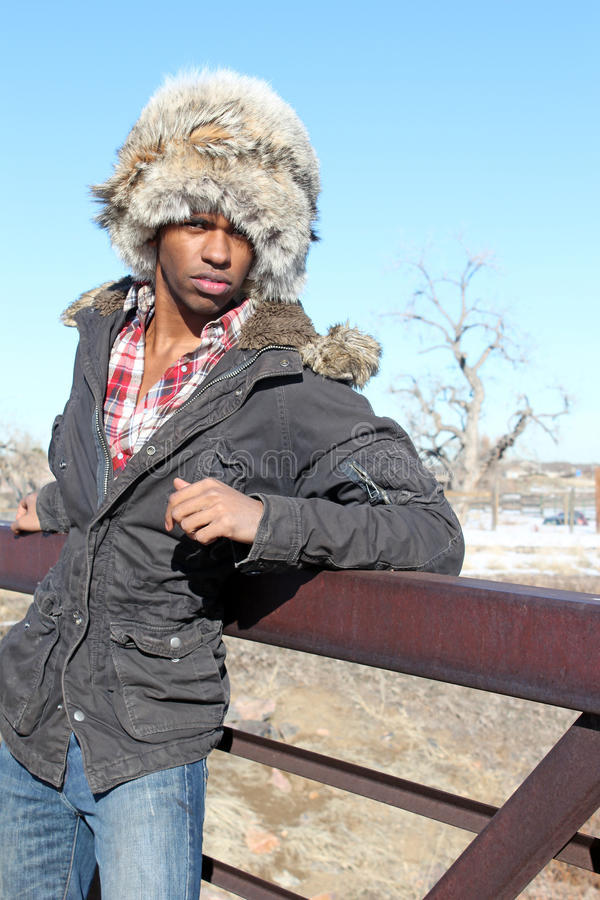 Man with Fur Cap. A black man in a fur cap and a winter parka leans against a bridge rail stock images