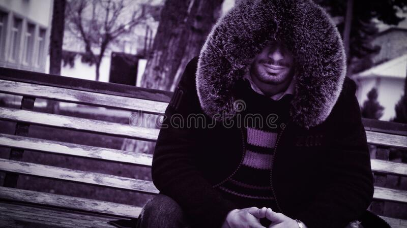 Man with fur collar on bench stock image