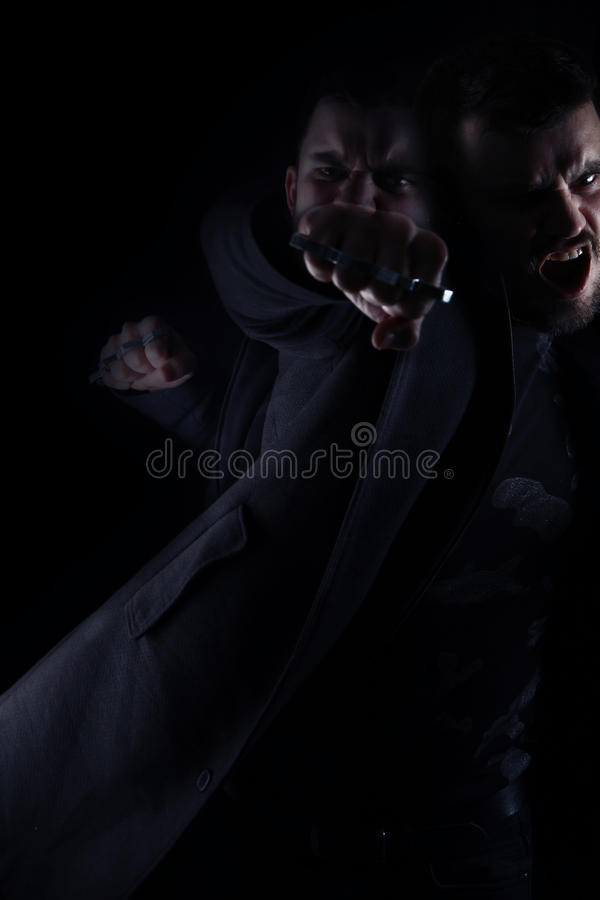 Man furious giving a punch. On a black background royalty free stock photo